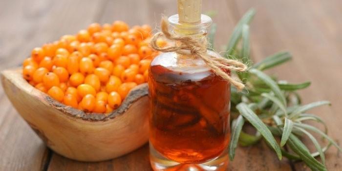 Масло облепихи в бутылочке и плоды облепихи