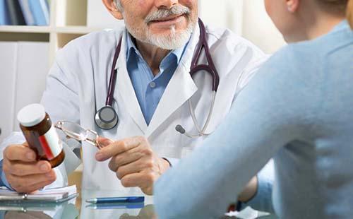Рука доктора держит флакон с не внушающим доверие содержимым