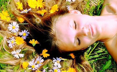 Девушка рассыпала волосы среди душистых трав