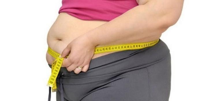 Полная женщина измеряет объем талии сантиметром