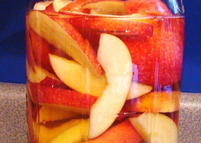 Наполнить яблоками банки и залить спиртом