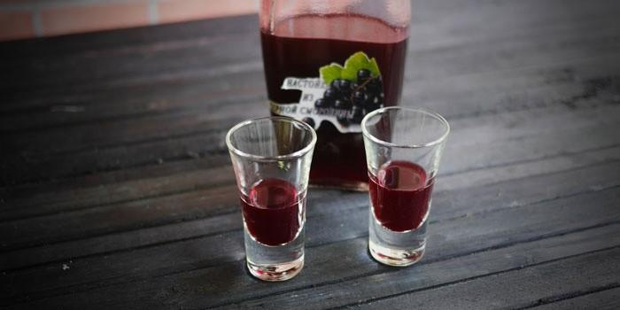 Смородиновая настойка в бутылке и рюмках
