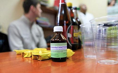 На столе находятся конфеты в жёлтой обёртке, бутылки и пузырёк настойки