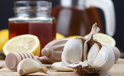 Дольки чеснока, лимон и мед