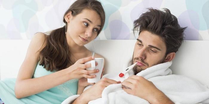 Девушка протягивает больному парню чашку с питьем