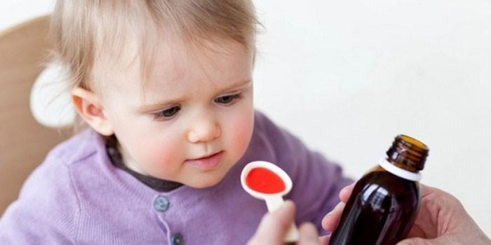 Ребенку дают сироп в мерной ложечке